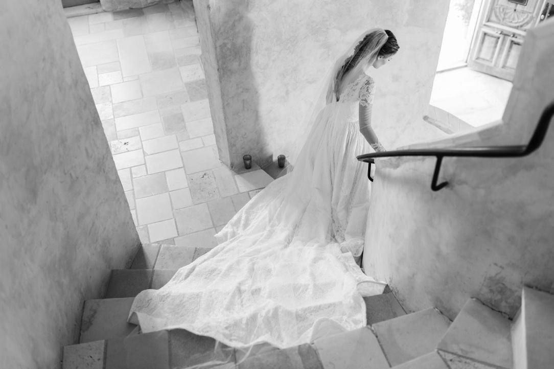 Bride Alyssa Campanella walks down a spiraling stone staircase at Sunstone Villa in her custom Lauren Elaine wedding gown and veil