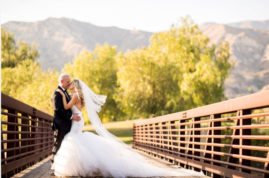 A bride wears a custom Lauren Elaine mermaid backless mermaid wedding gown with cathedral tulle train and veil in Los Angeles, CA at Angeles National Golf Club.