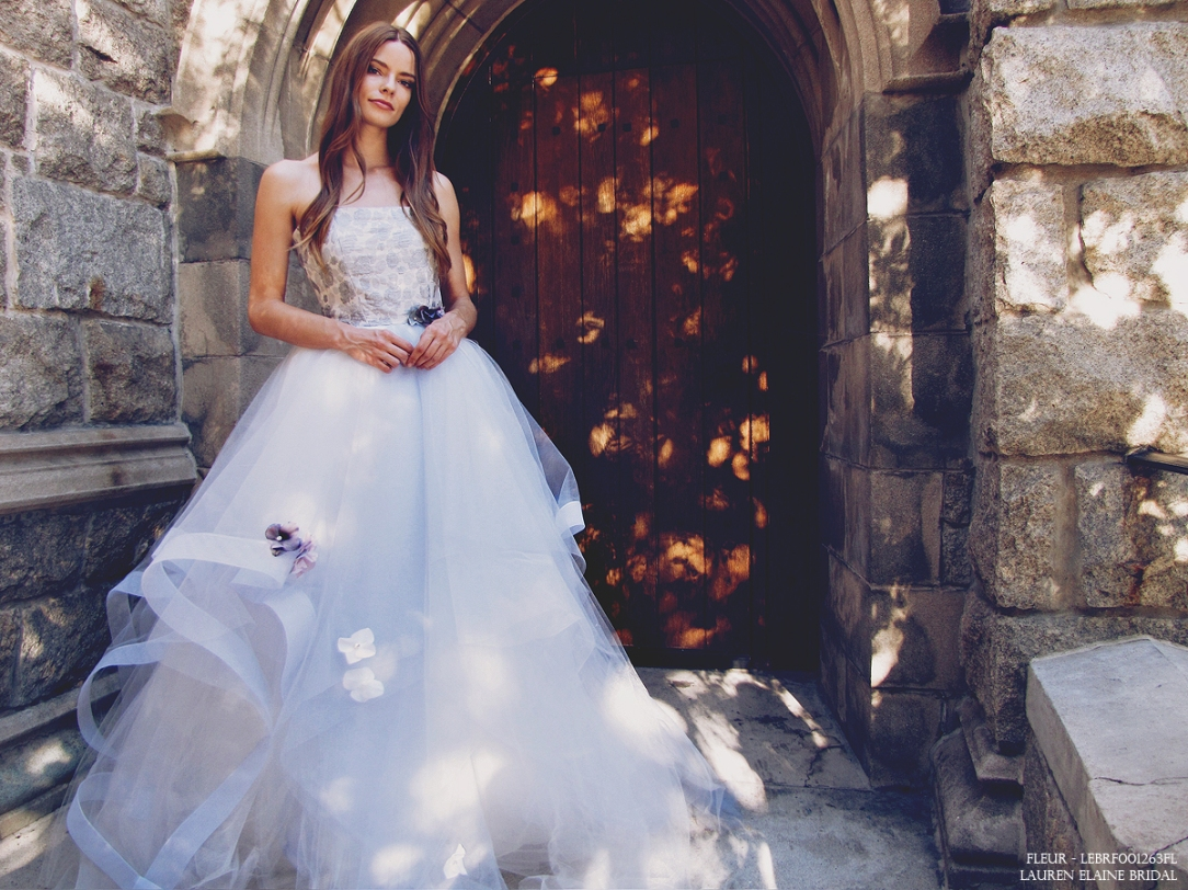 """Lauren Elaine """"Fleur"""" wedding gown with blue tulle skirt and horsehair petals. Crystal and pearl beading and flowers on skirt."""