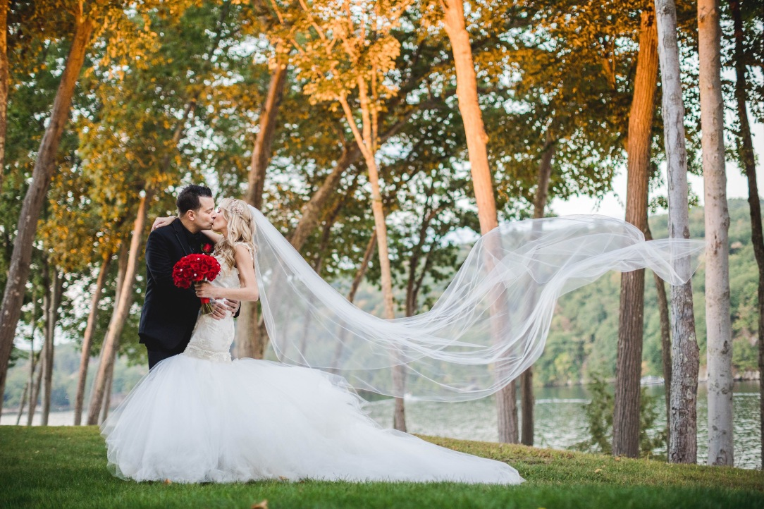 Bride Jenny wears the Lauren Elaine Wisteria gown with cathedral length veil and red bouquet