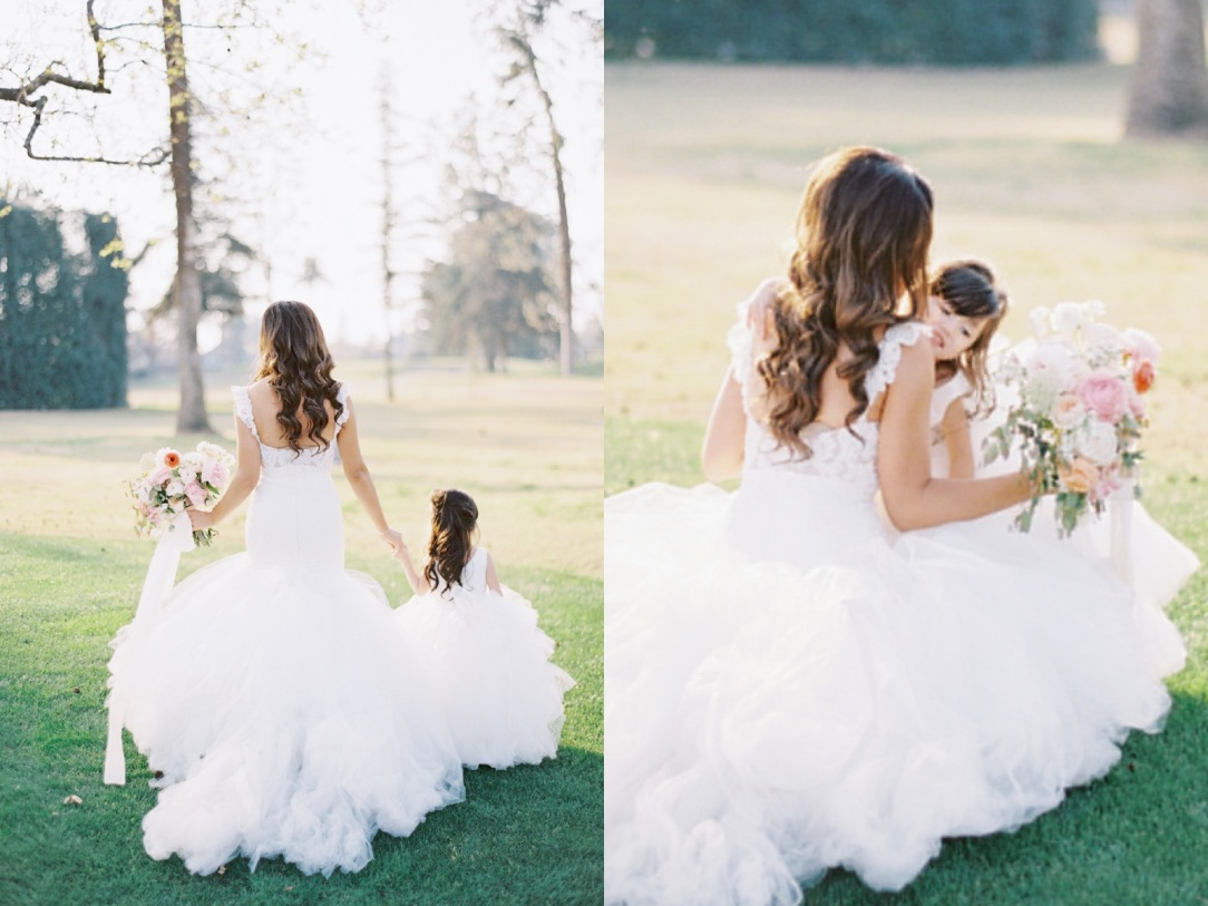 Matching bride and flower girl in tulle dresses exchange kisses and hugs