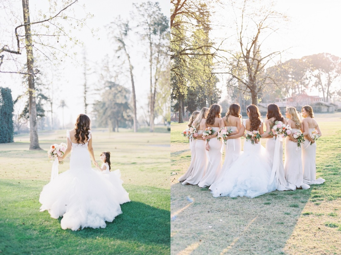 A bride wears a tulle lace mermaid wedding dress with cathedral train with her bridal party in blush glowns