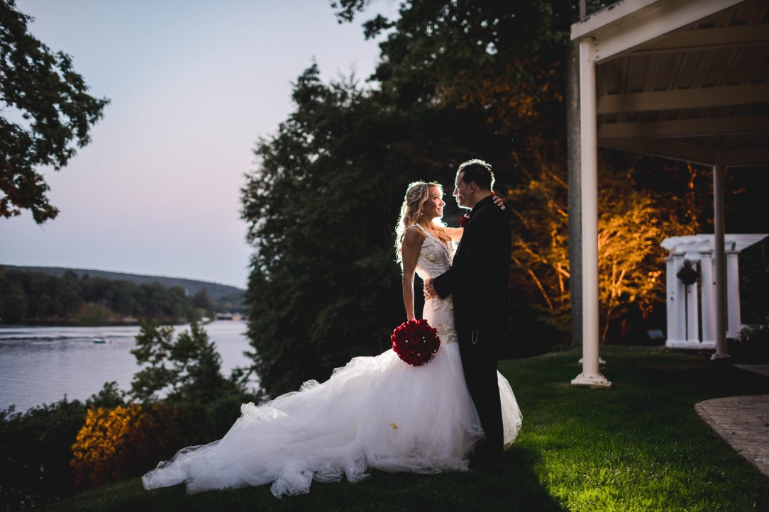 Bride Jenny embraces husband nick with red bouquet in her custom lauren elaine wisteria bridal gown wedding dress