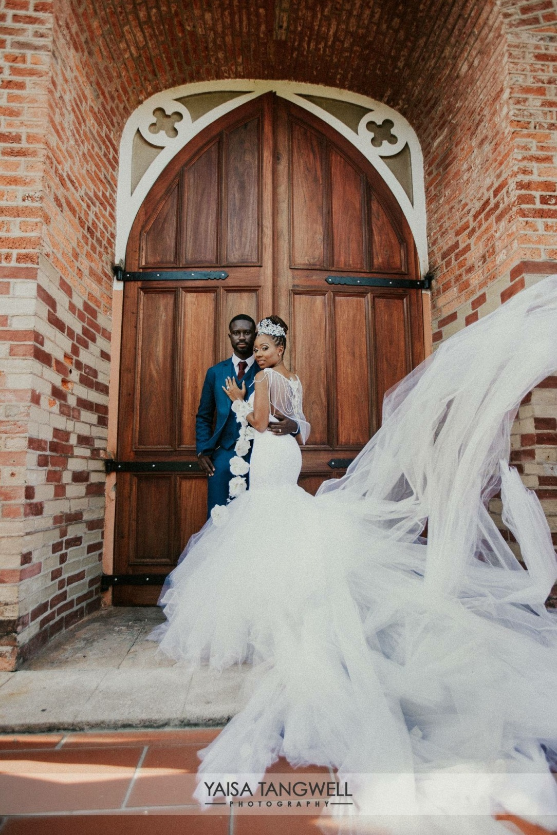 Bride Lynnel wears a custom Lauren Elaine Bridal Jasmine wedding dress gown with cathedral tulle train and crown blowing in the wind