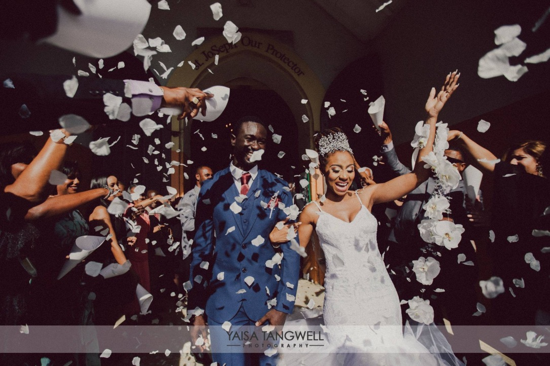 A bride and groom exit church wedding under confetti