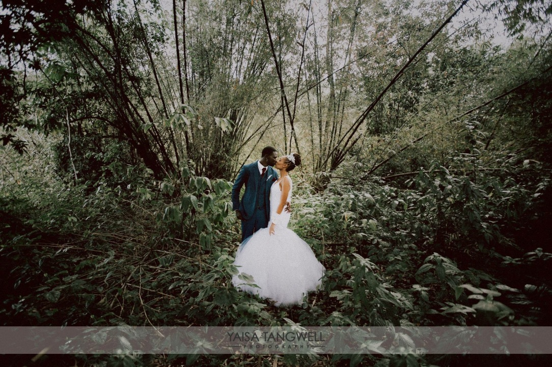 Bride and groom embrace in an enchanted fairytale forest for their Caribbean wedding