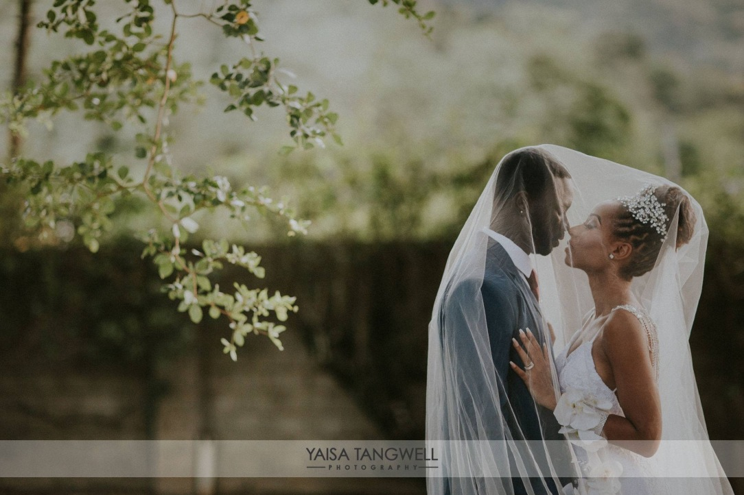 Bride and groom underneath veil by Yaisa Tangwell