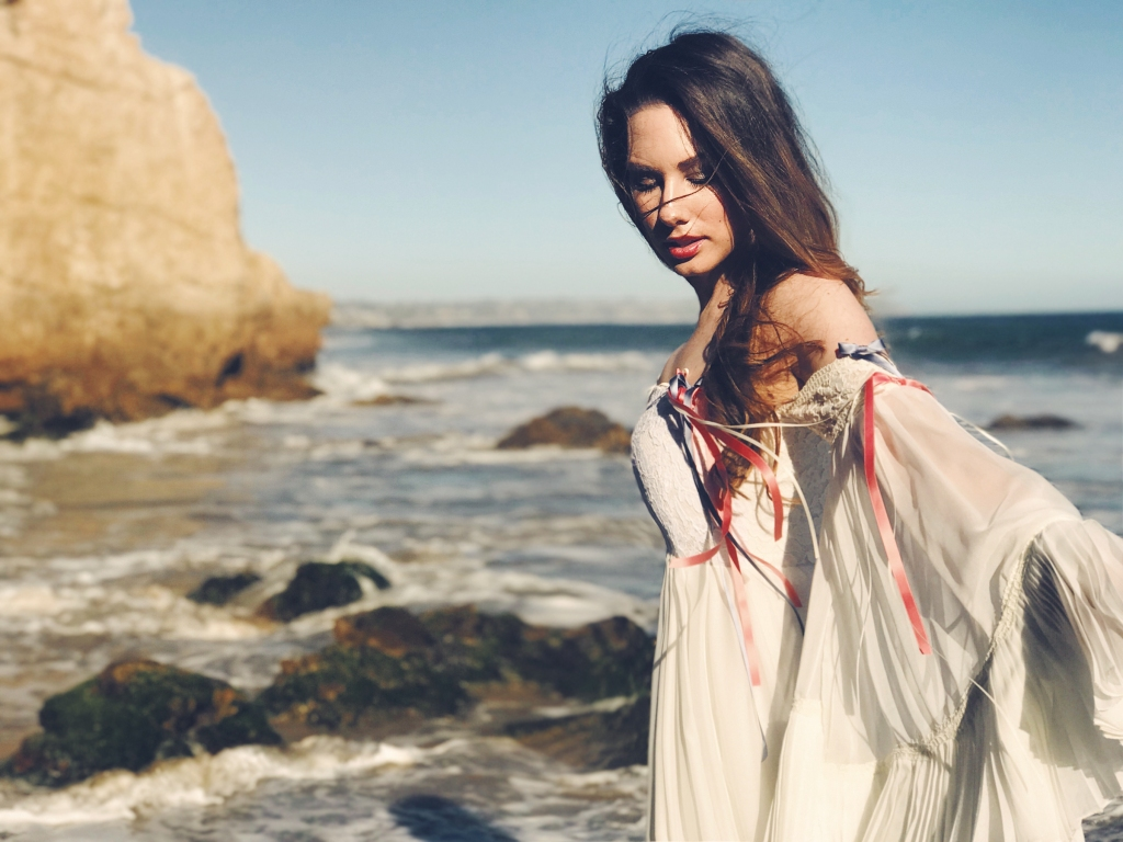 Designer Lauren Elaine poses for a fashion editorial feature at el matador beach in malibu in an ethereal wedding gown