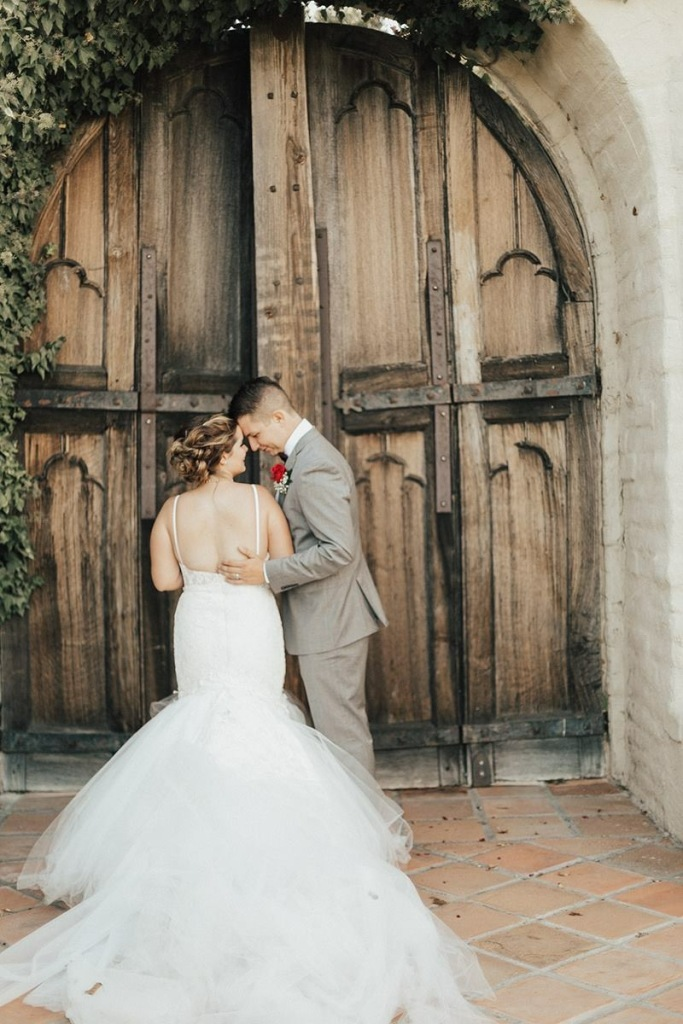 Bride Allyson wears a Lauren Elaine wedding gown with detachable cathedral train at Whispering Rose Ranch.