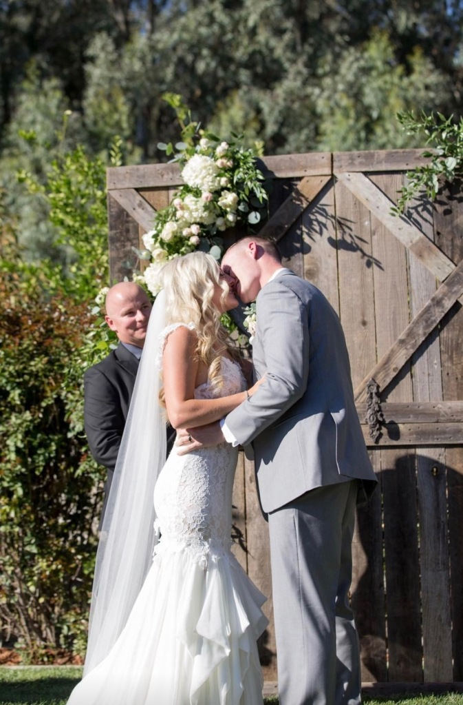 Bride Keri and Husband Tyler embrace at their Chico, California wedding.