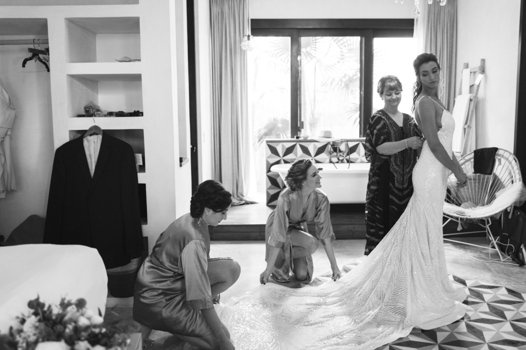 "A bridal party helps bride Geniffer get ready in her custom Lauren Elaine ""Prism"" gown."