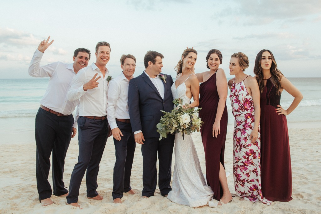 A wedding party celebrates on a beach in Mexico.