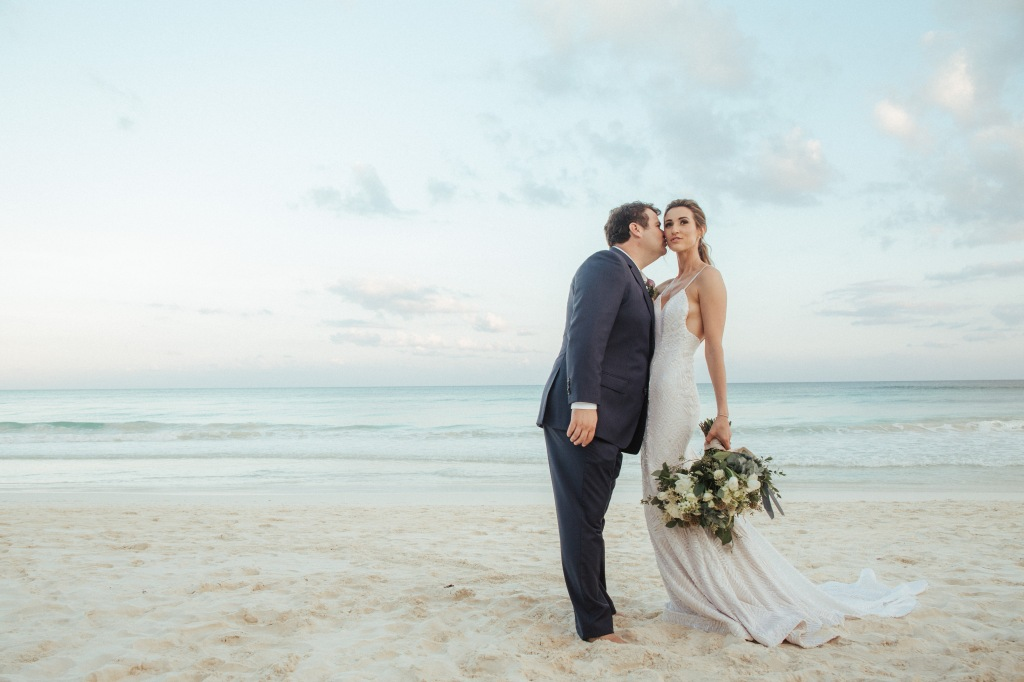 "Bride Geniffer poses in her custom Lauren Elaine ""Prism"" wedding gown on a beach in Mexico."