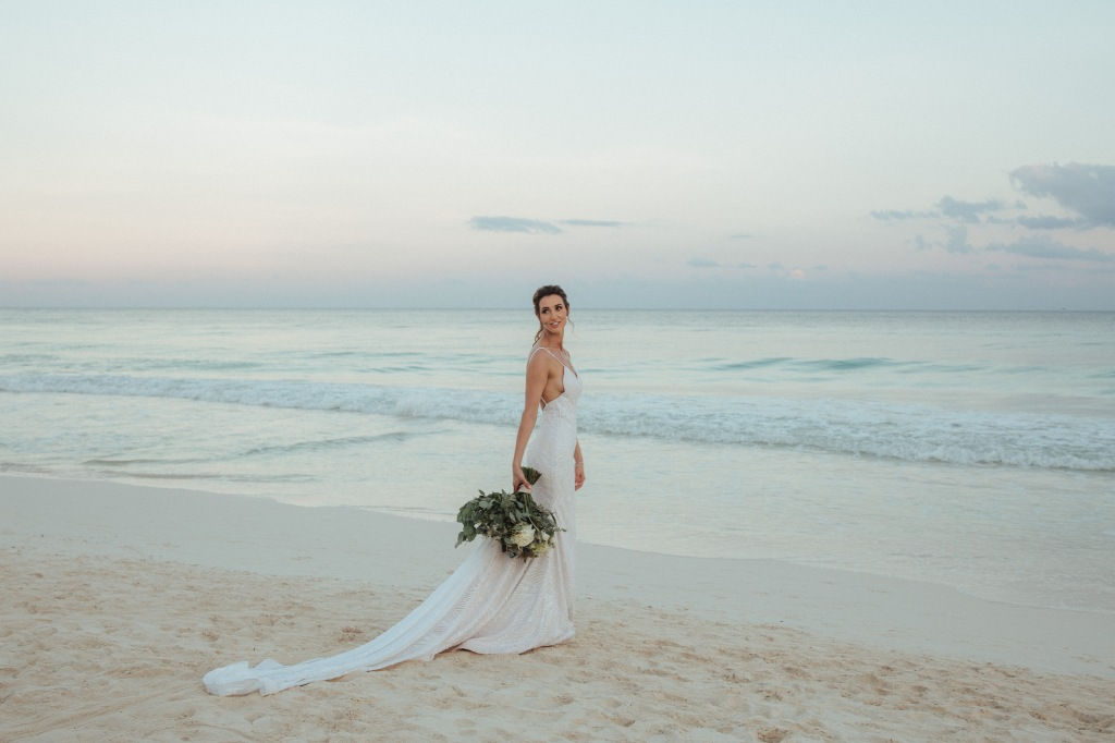 "Bride Geniffer poses in her custom Lauren Elaine ""Prism"" wedding gown on a beach in Mexico with 5ft sequin cathedral train."