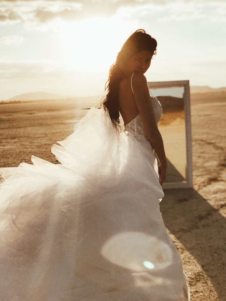 A model poses in front of a mirror at el mirage dry lake bed in California wearing a lauren elaine mermaid wedding dress